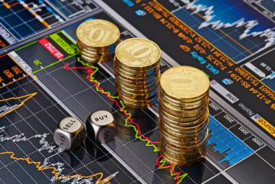 Kostki ze słowami sell i buy oraz stosy monet jako symbol rolowania kontraktów CFD