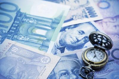 Banknoty i zegarek jako symbol tradingu na forex w danym czasie